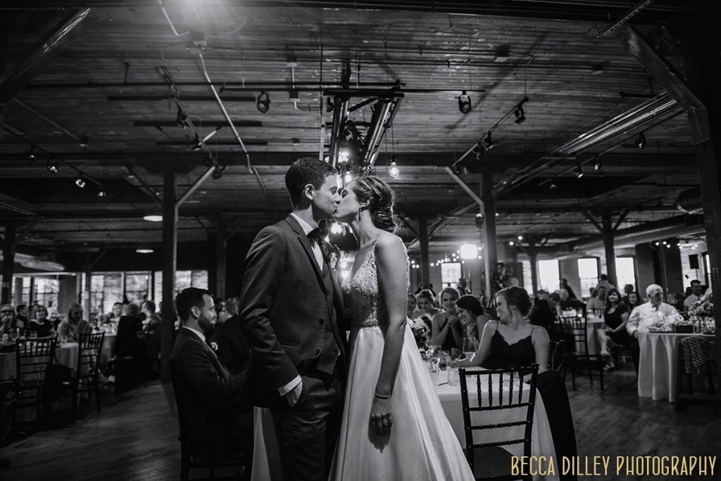 brid eand groom share a kiss in the industrial interior of  solar arts wedding reception