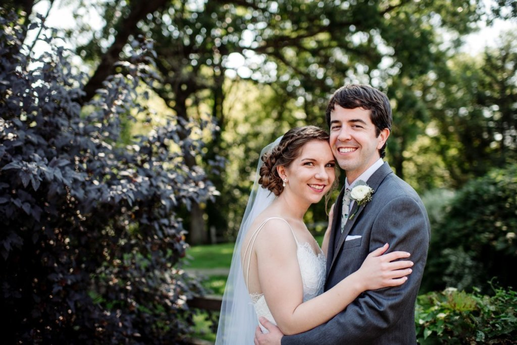 bride and groom hug in front of treesvoyageur wedding environmental center mn
