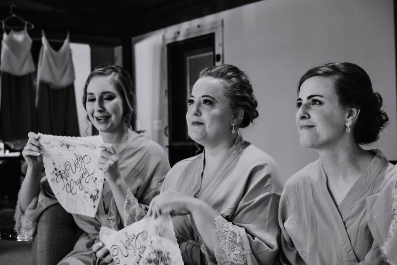 black and white image of bridesmaids laughing and holding hankerchiefs voyageur wedding environmental center mn