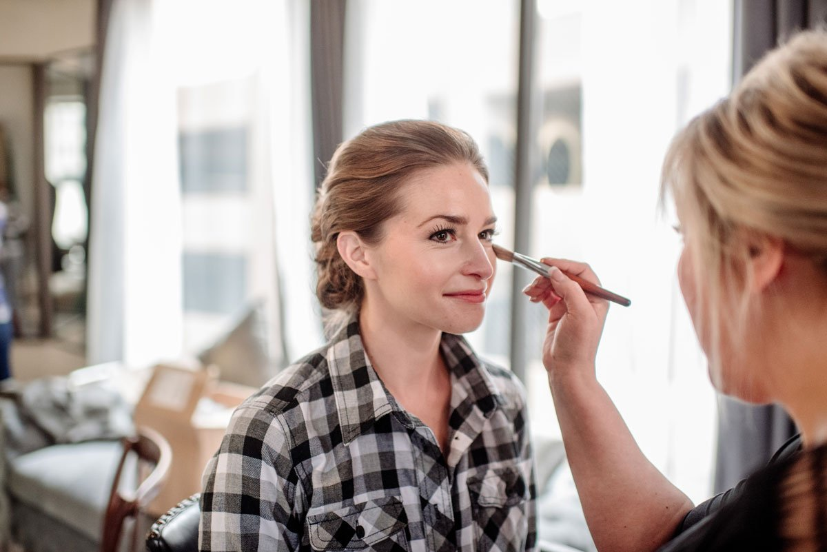 bride getting makeup finished in rooms at lumber exchange minneapolis before wedding