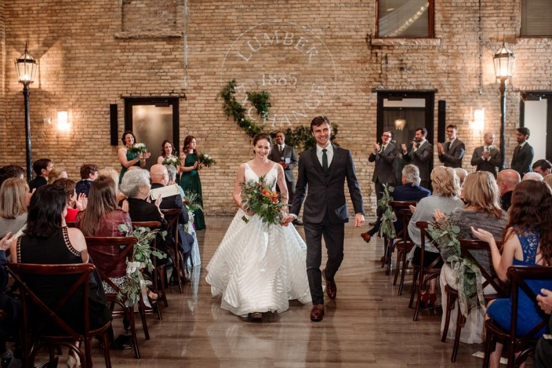 Bride and groom walk down aisle after wedding ceremony at Lumber Exchange