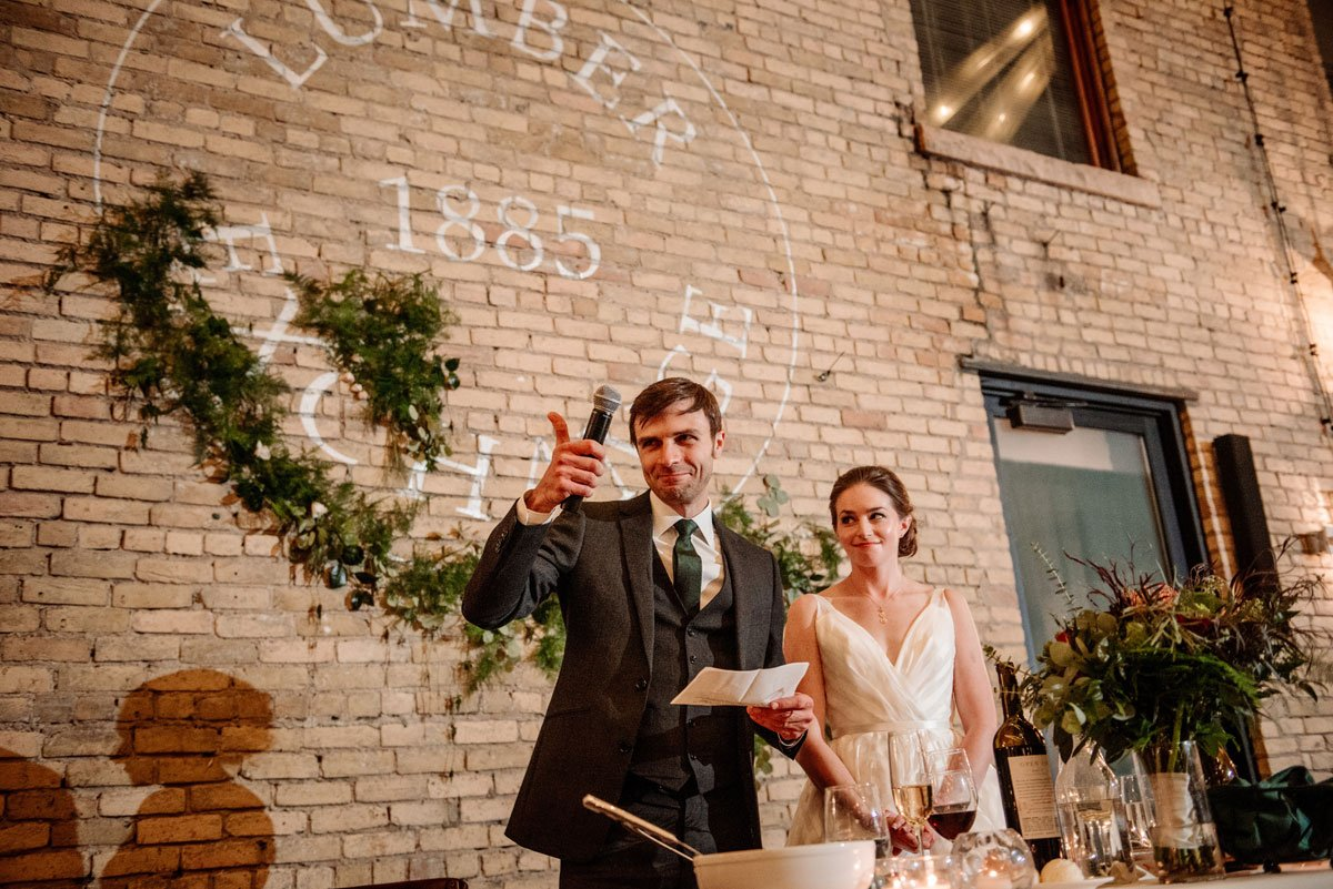 bride and groom stand to give speeches at lumber exchange wedding reception
