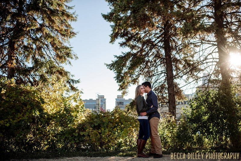 tall piine trees behind couple at st anthony main fun engagement photo ideas minneapolis