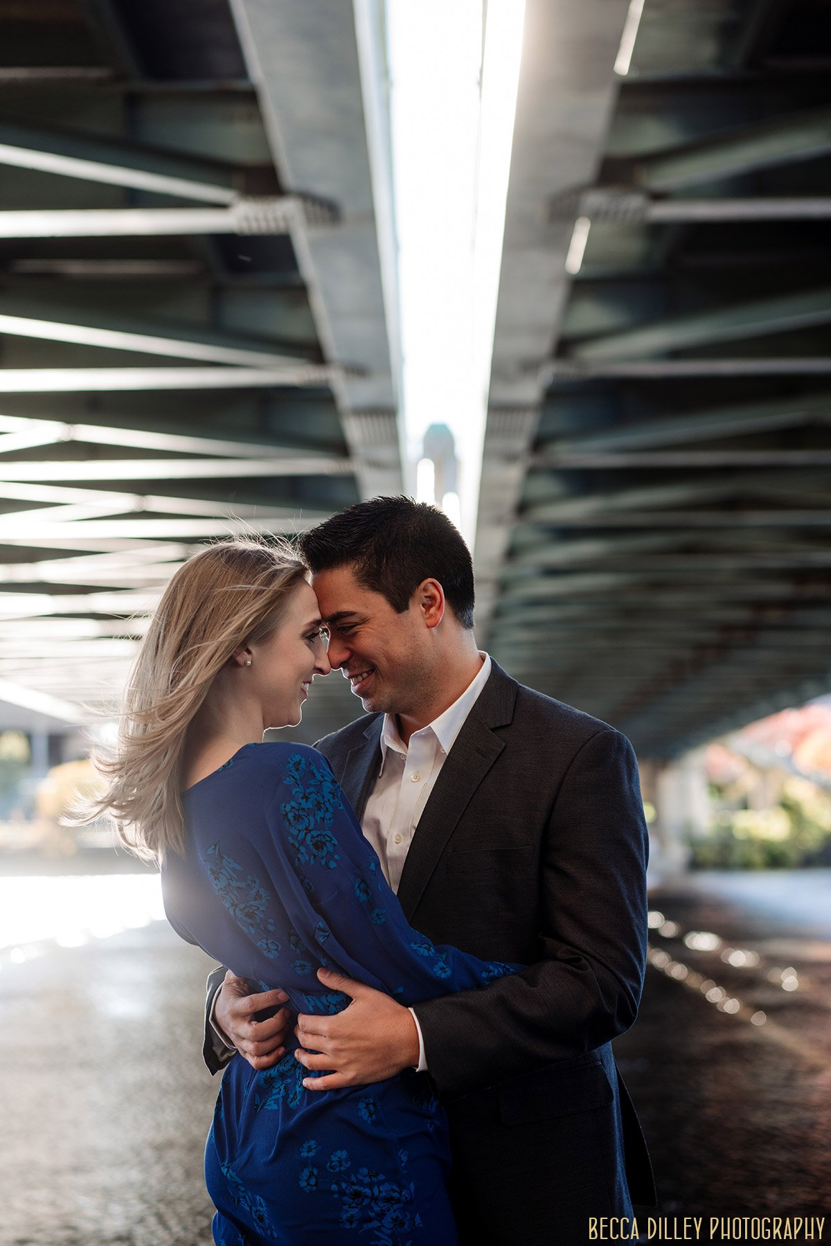 couple holds each other under bridge on nicollet island fun engagement photo ideas minneapolis