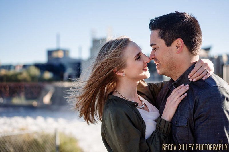 wind blows through Marissa's hair at Water Power Park for engagement photos with skyline