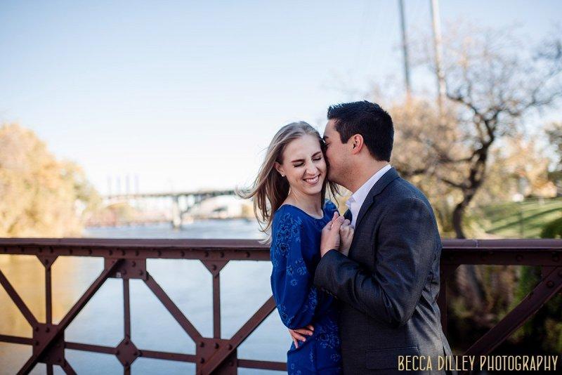 couple laughing on nicollet island bridge fun engagement photo ideas minneapolis