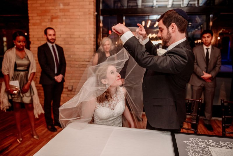 groom lifts veil after ketubah signing minneapolis event center