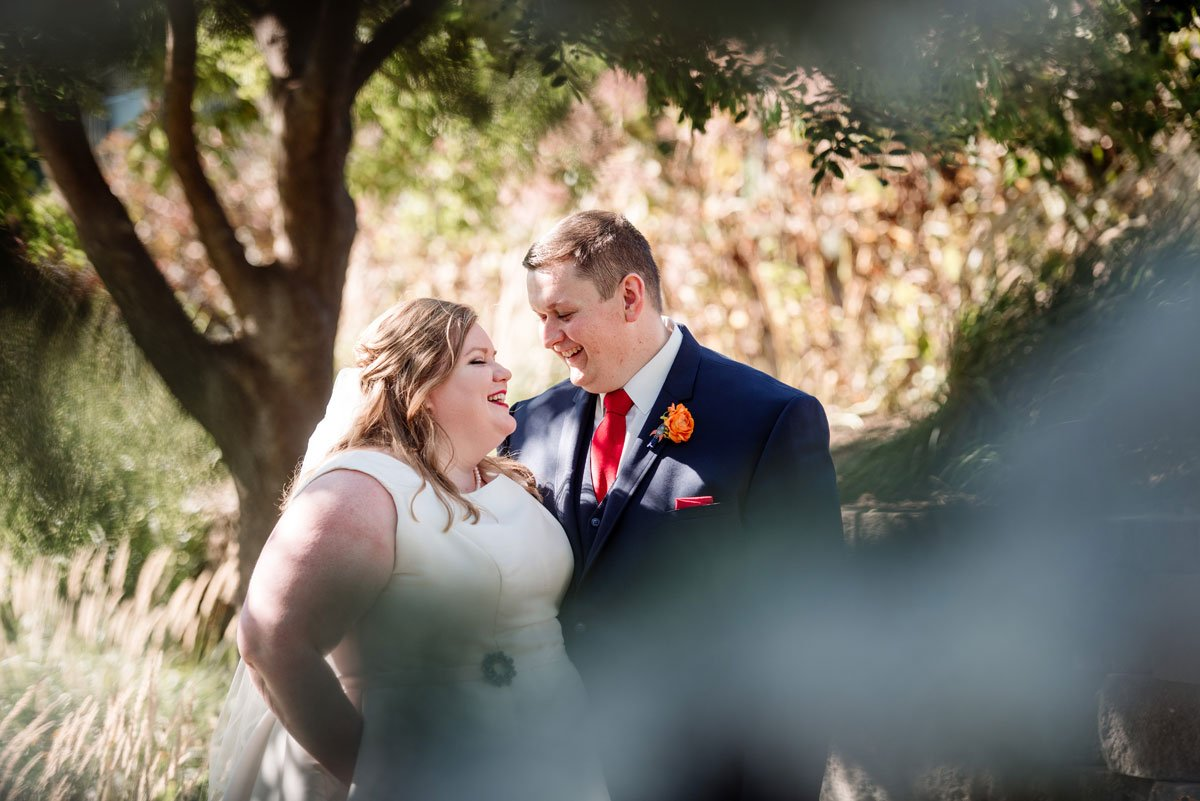 bride and groom embrace between trees in summer time wedding sioux falls