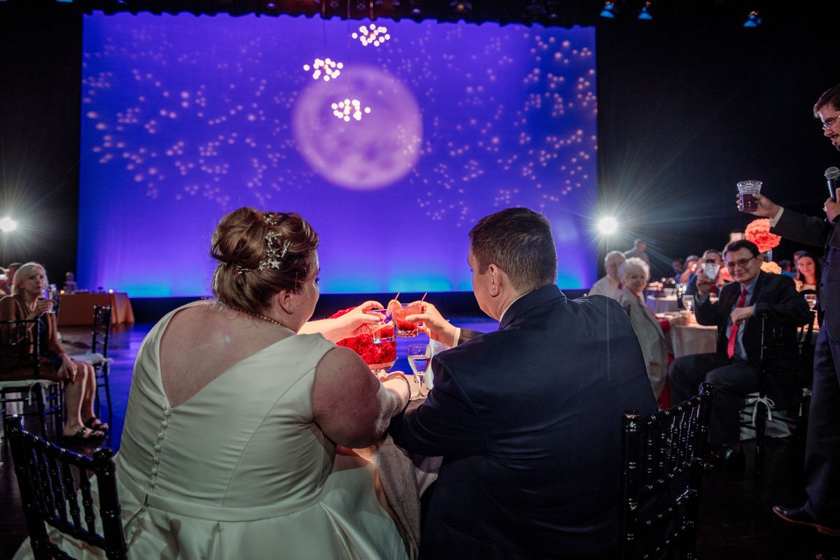 bride and groom toast in front of projection of moon at washington pavilion wedding sioux falls