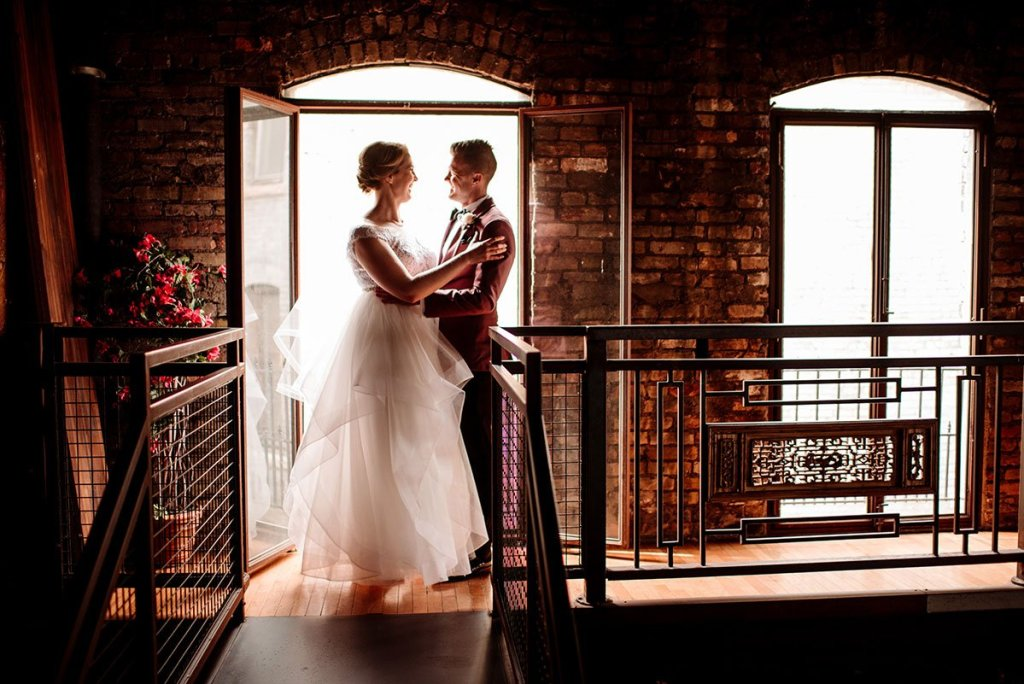 sun streams behind couple on balcony of loring restaurant wedding minneapoils