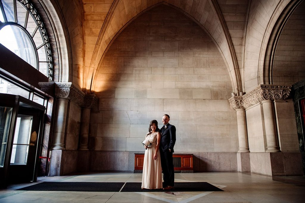 minneapolis city hall elopement couple under large stone arches Minneapolis City Hall Wedding
