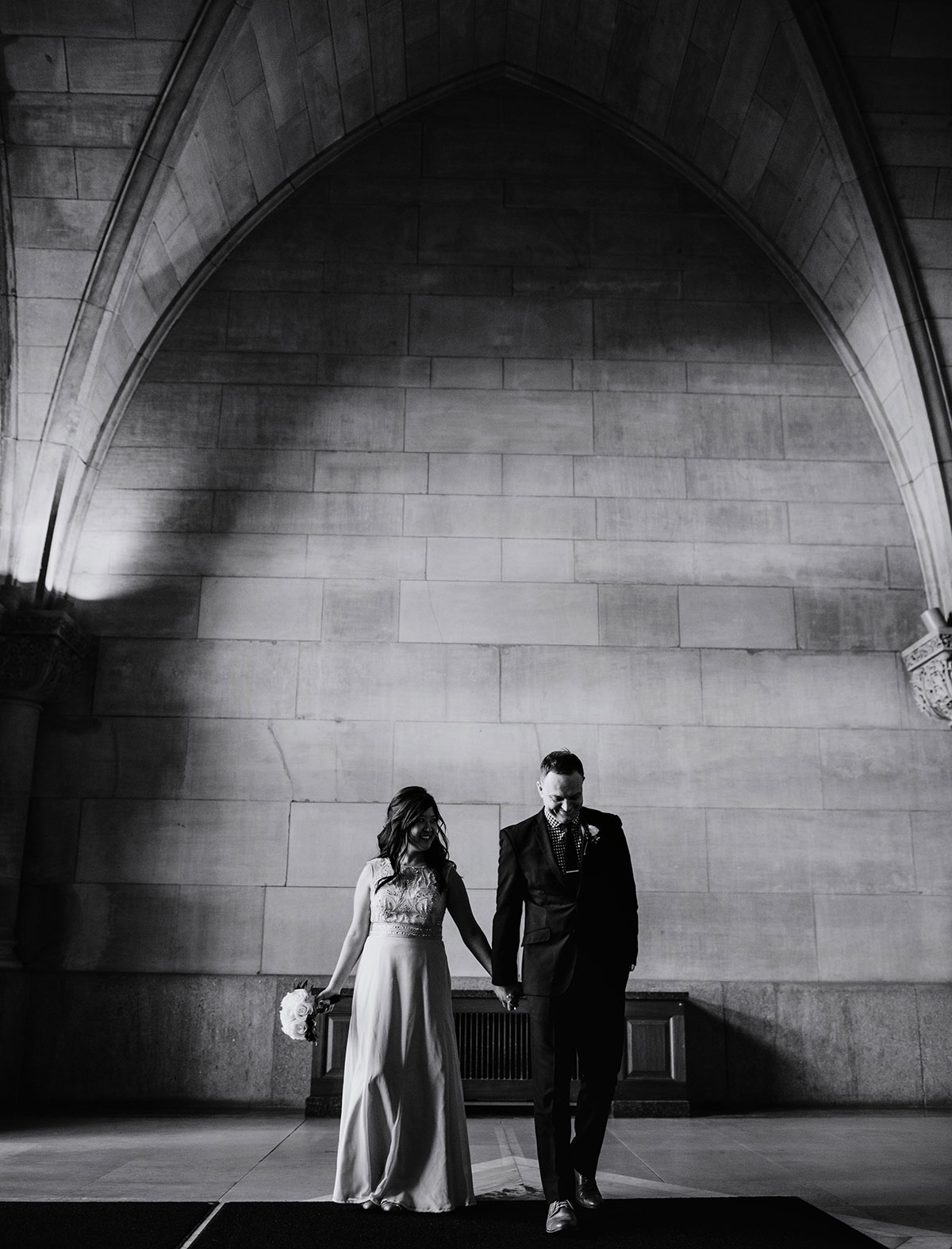moody black and white portrait of couple walking inside Minneapolis City Hall Wedding