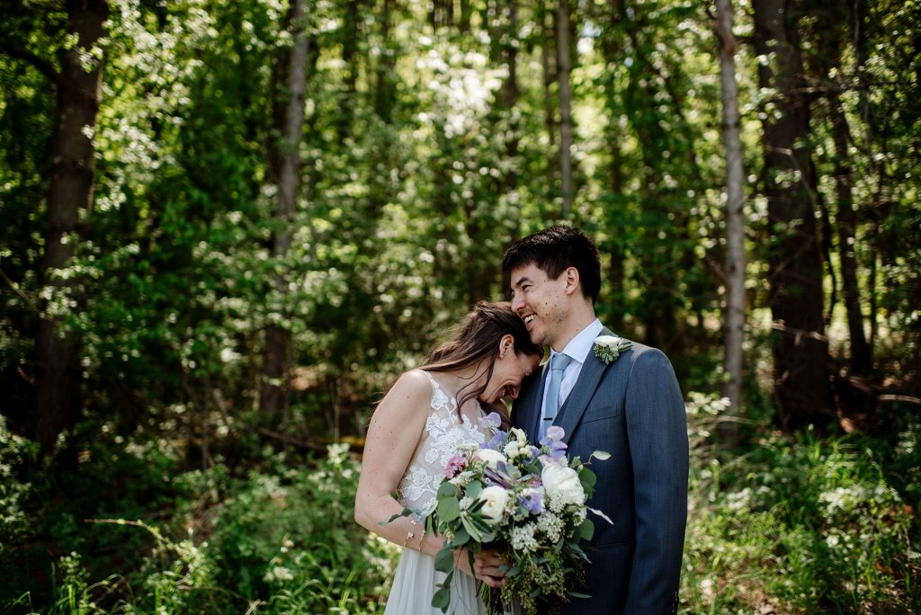 couple in woods in summer wedding at round barn