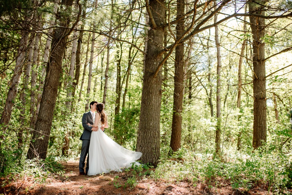 pine forest with couple kissing before wedding ceremony