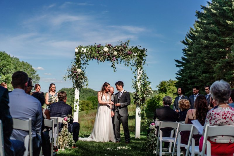 bride and groom with floral arbor wedding at round barn