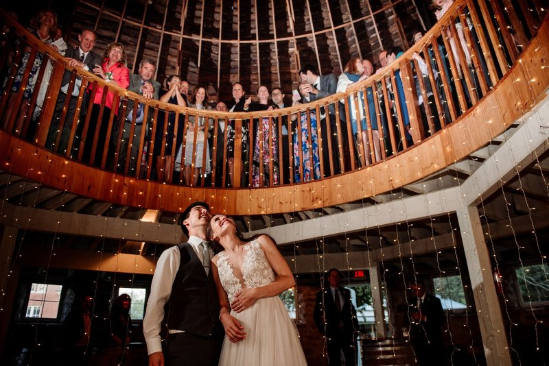 bride and groom under balcony of round barn wedding in MN