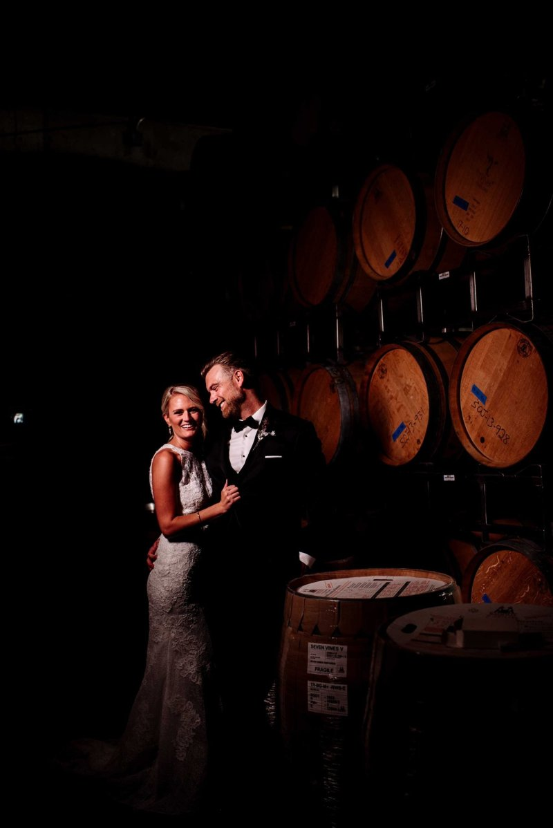 bride and groom by wine casks