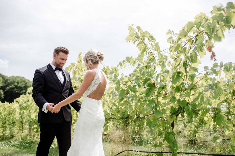 bride and groom first look among vines at 7 vines vineyard wedding mn