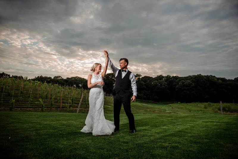 groom spins bride in dance outside at 7 vines vinyard wedding mn