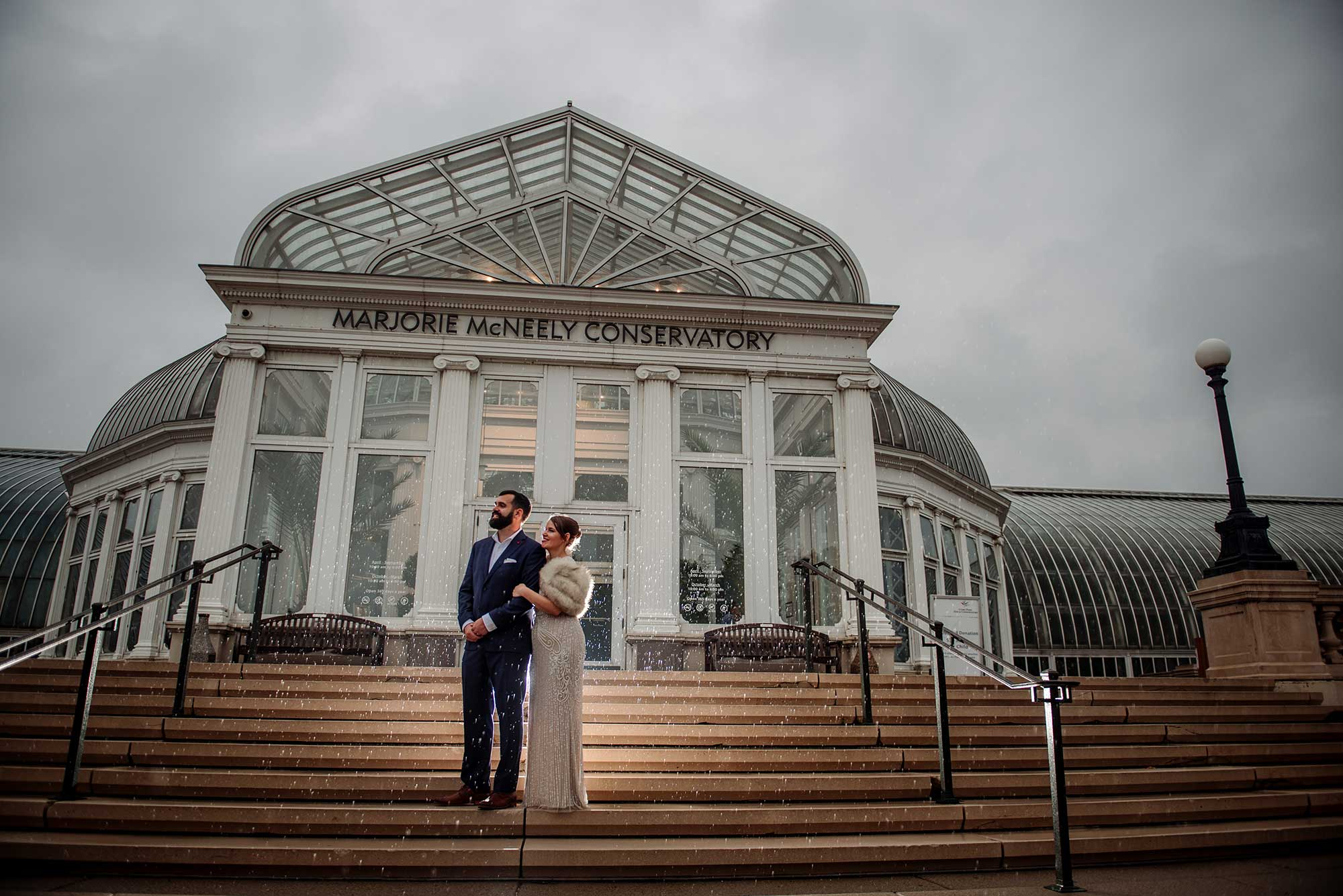 wedding couple in rain outside of como conservatory after small wedding