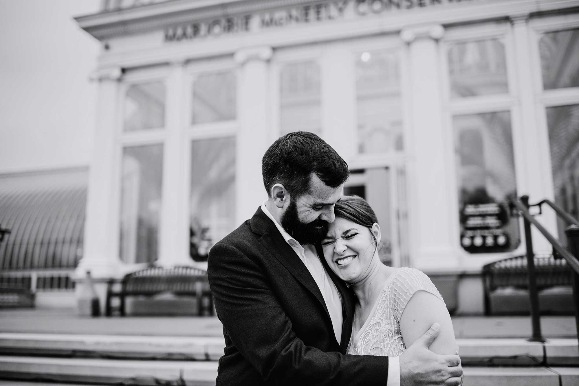 black and white photo of bride and groom laughing outside como conservatory out