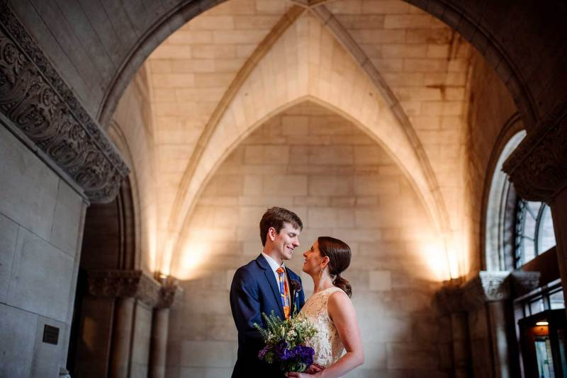 embrace under the vaulted ceilings at Minneapolis city hall wedding