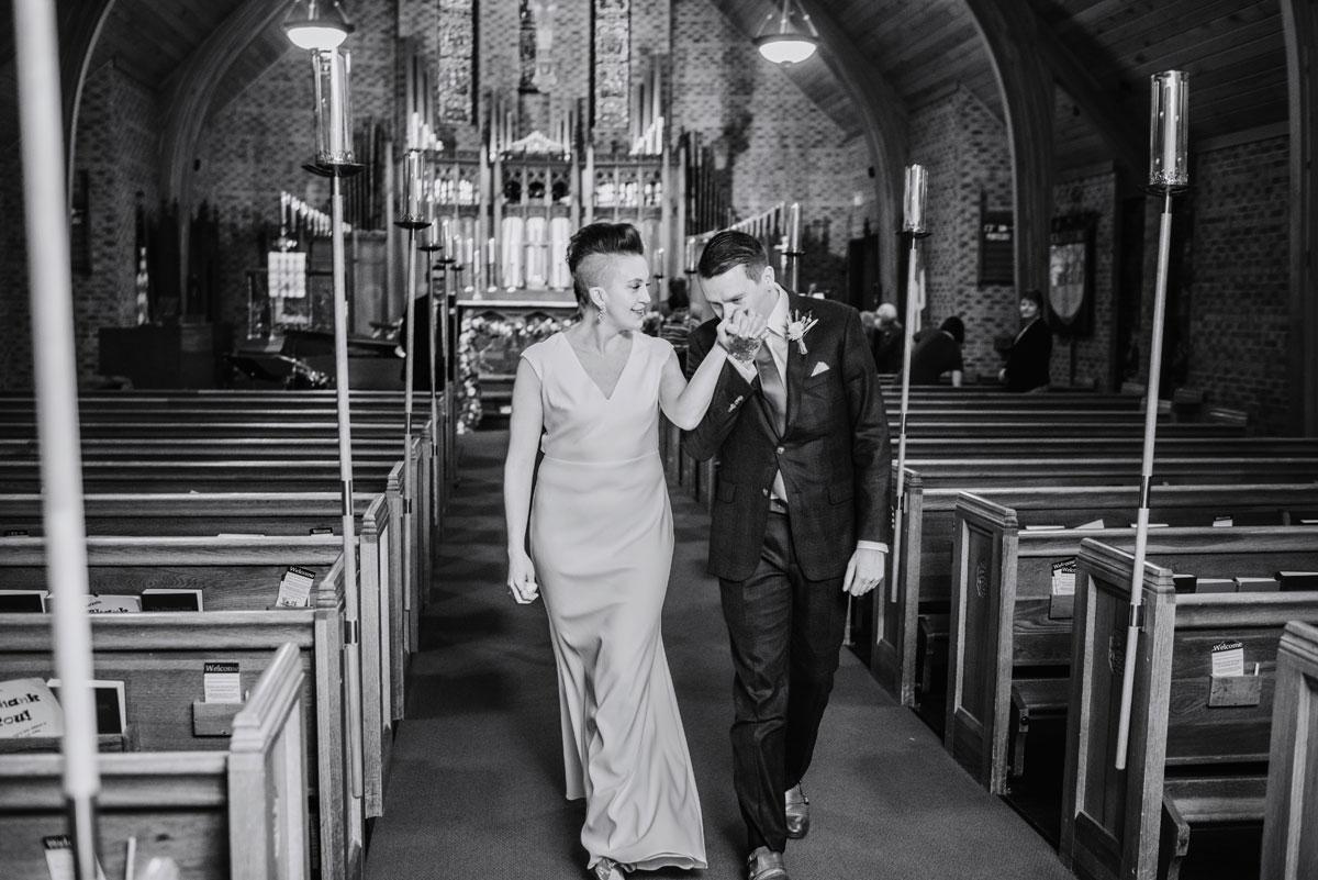walking down the aisle, groom kisses brides hand