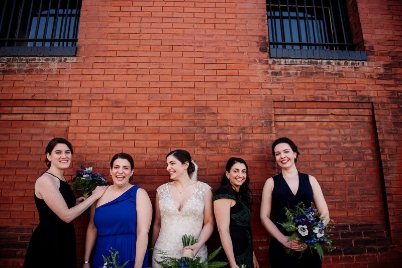 bridesmaids at side of building