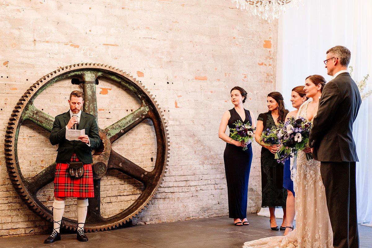wedding ceremony with speaker in red kilt