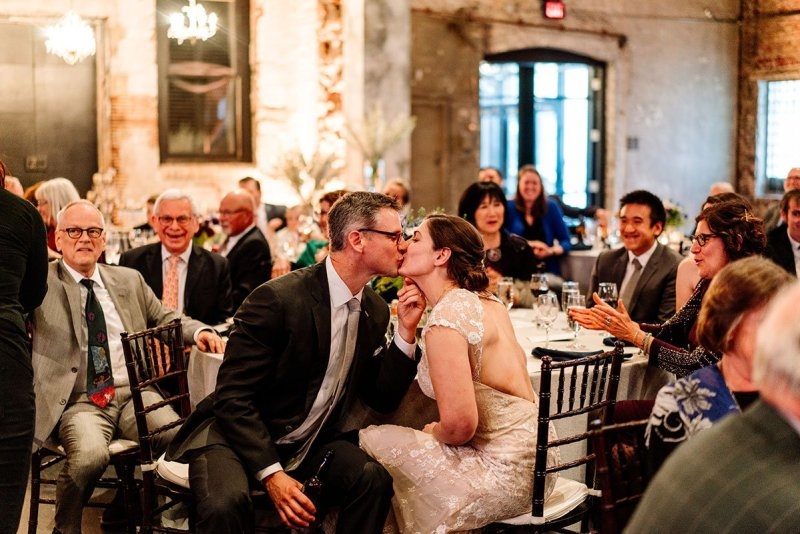 bride and groom kiss during toasts aria wedding minneapolis