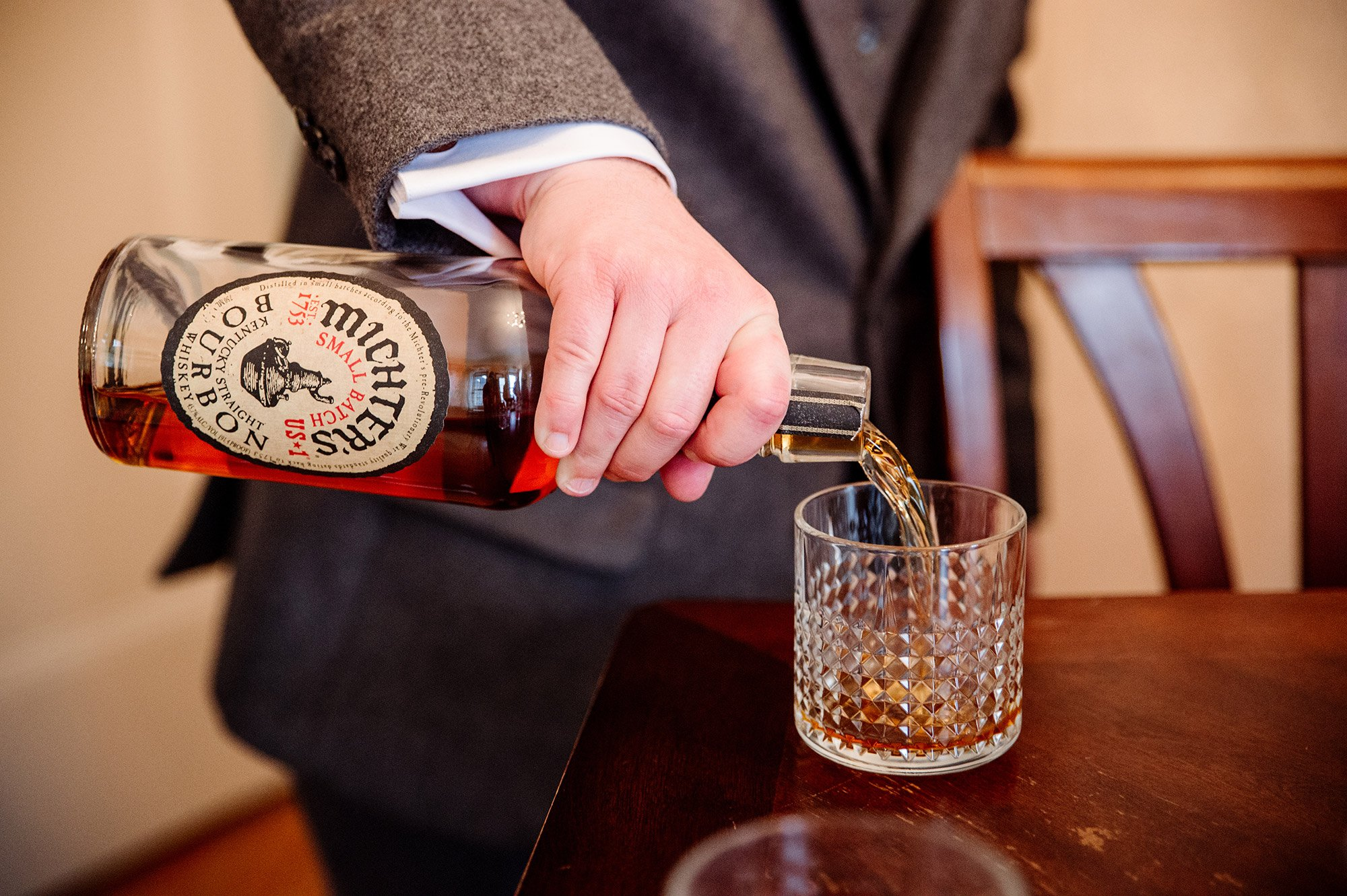 pouring out a glass of whiskey before st paul college club wedding