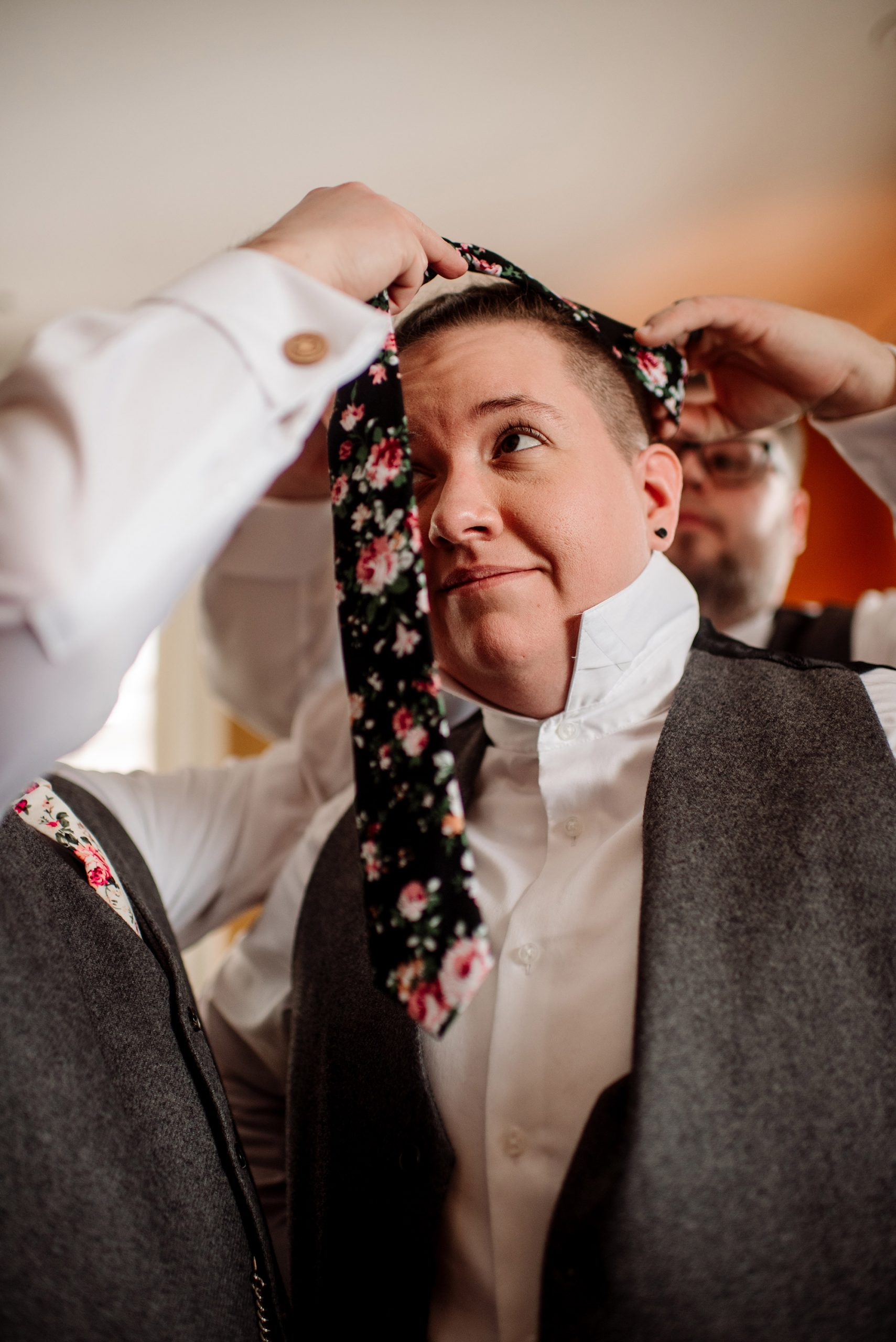 butting on floral tie before st paul college club wedding mn lgbtq photographer