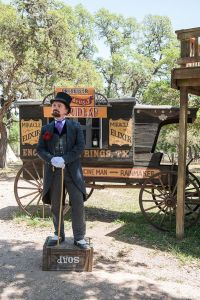 Snake oil salesman historical reactor standing on a soap box in front of a carriage