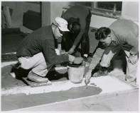 Nivola and assistant pouring concrete into the finished forms, circa 1960