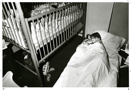 A mother sleeps on the floor next to her child's crib, circa 1975. Before the new hospital building opened in 1984, there were no designated spaces for parents rest when they visited their children and they often resorted to napping on the floor.