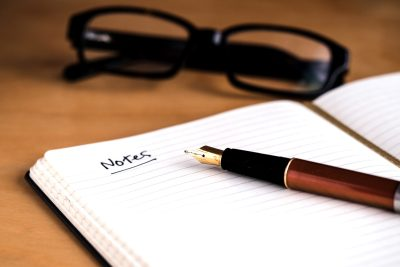 "The top half of an open A5 lined notepad is in the foreground of the image, on a light wooden table. There is a fountain pen laying on the notepad, and a title of ""Notes"" has been written. In the background, black framed glasses can be seen sitting on the table."