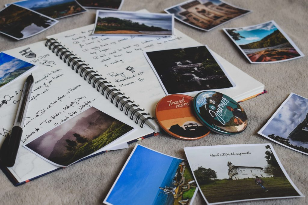 Picture of a notebook with printed pictures laying around it