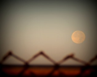 ....Looking at the full moon with the fence in the foreground.