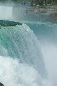The water rushes over the edge of the falls.