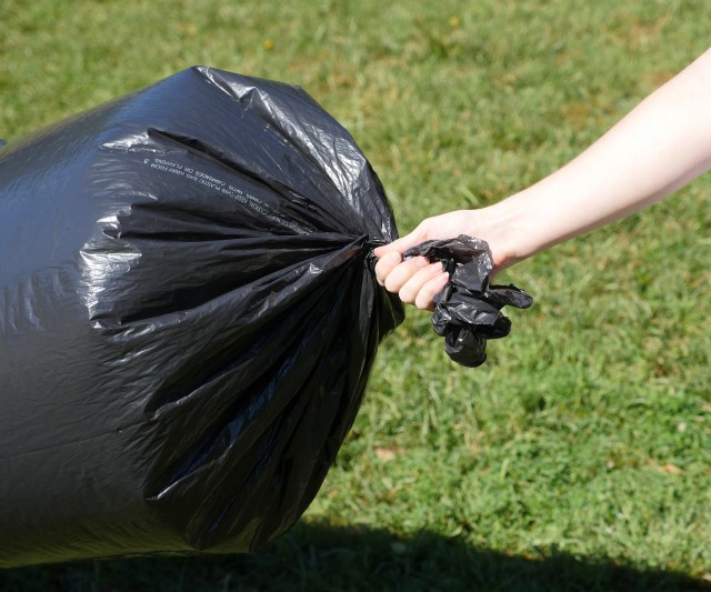 Image of trash bag balloon with ends gathered in preparation for tying
