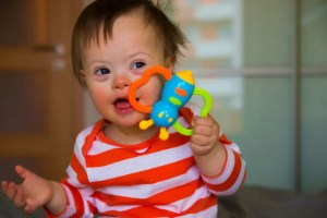Down syndrome baby playing at home