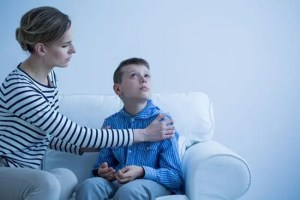 Young child with autism looking away from mother trying to talk to him