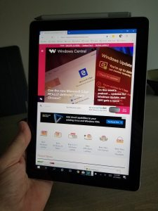 holding a surface go in one hand