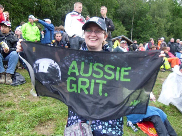 """Rebecca holding her """"Aussie Grit"""" flag in support of Mark Webber at the Belgian Grand Prix"""