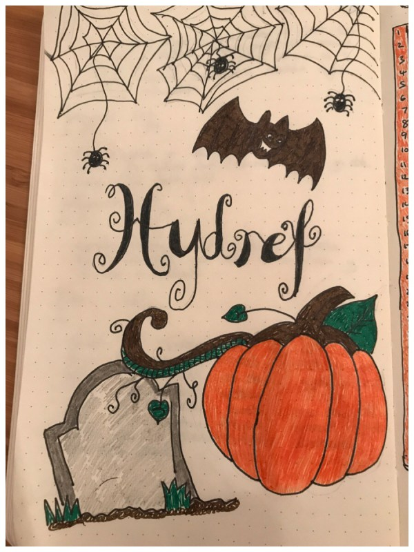 """Drawing of pumpkin, gravestone, bat and spiderwebs with the word """"Hydref"""" (October in Welsh) in calligraphy. My hello October page in the bullet journal."""