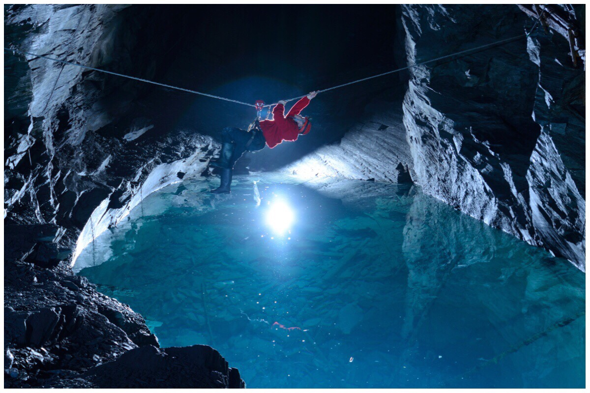 Man climbing along a rope over an underground lake