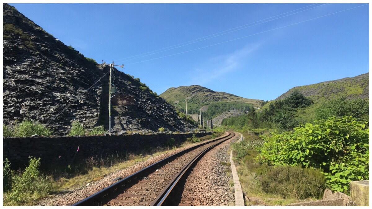 The Conwy Valley line heading off into the distance and past Pant Yr Afon Powerstation with slate tips to the left and greenery to the right