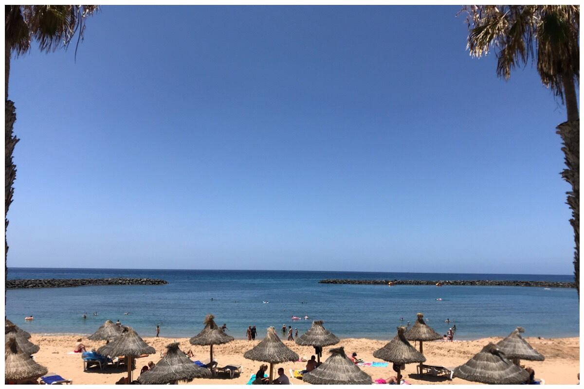 The beach and sea at Playa Las Americas, Tenerife with a beautiful blue sky in the background