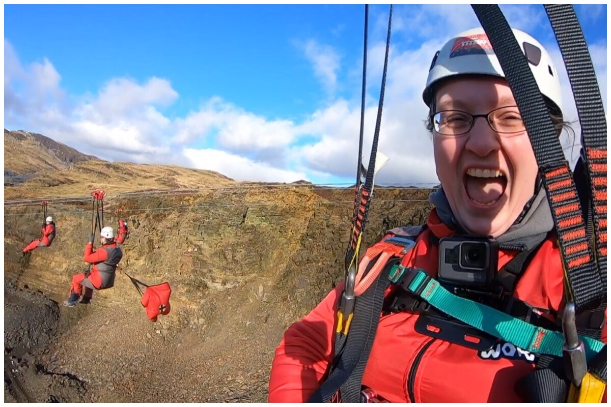 A photo of me (on the right) on Zipworld Titan's Bravo line. In the background is my husband and his parachute and behind him is the mountain and blue sky.
