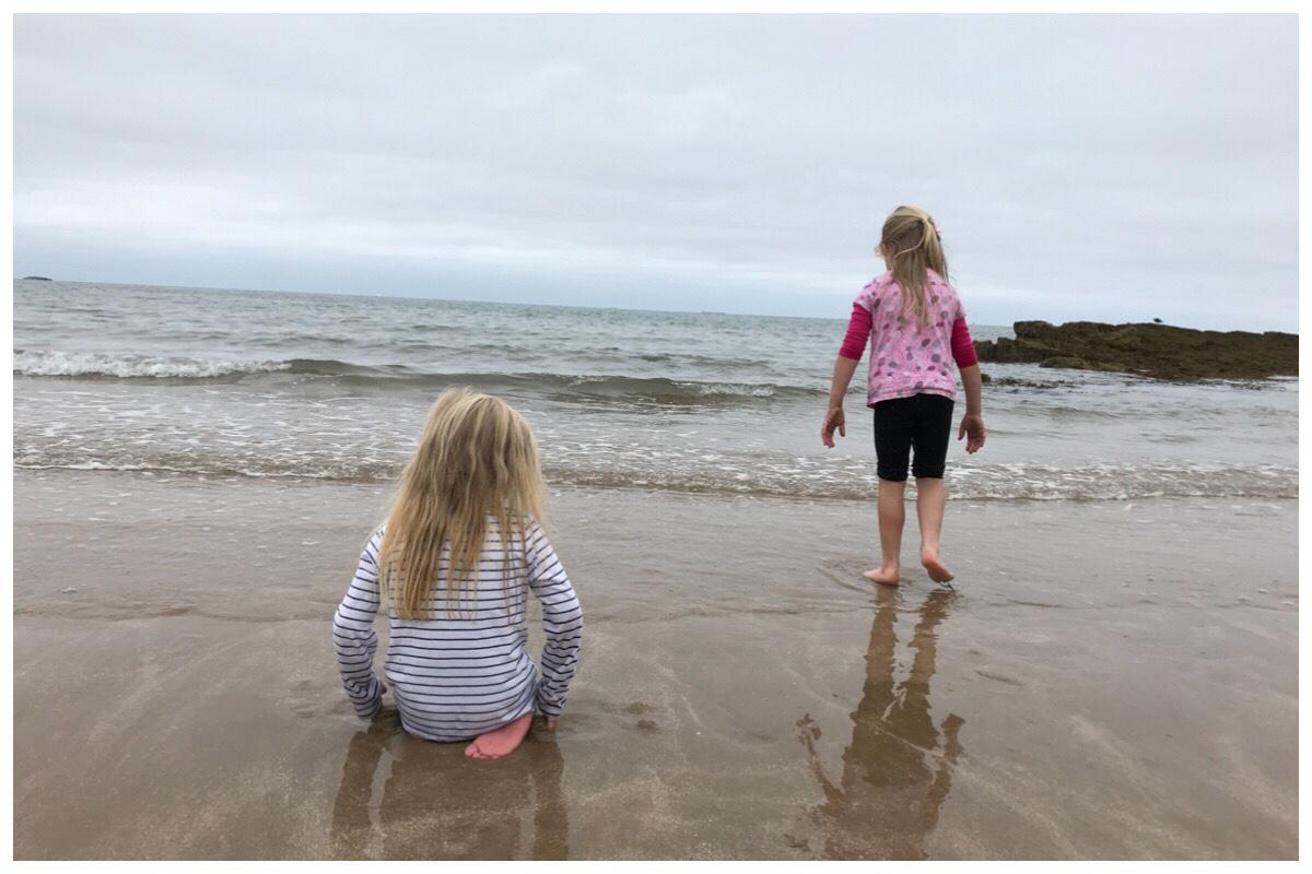 The girls sat/stood on Benllech beach.